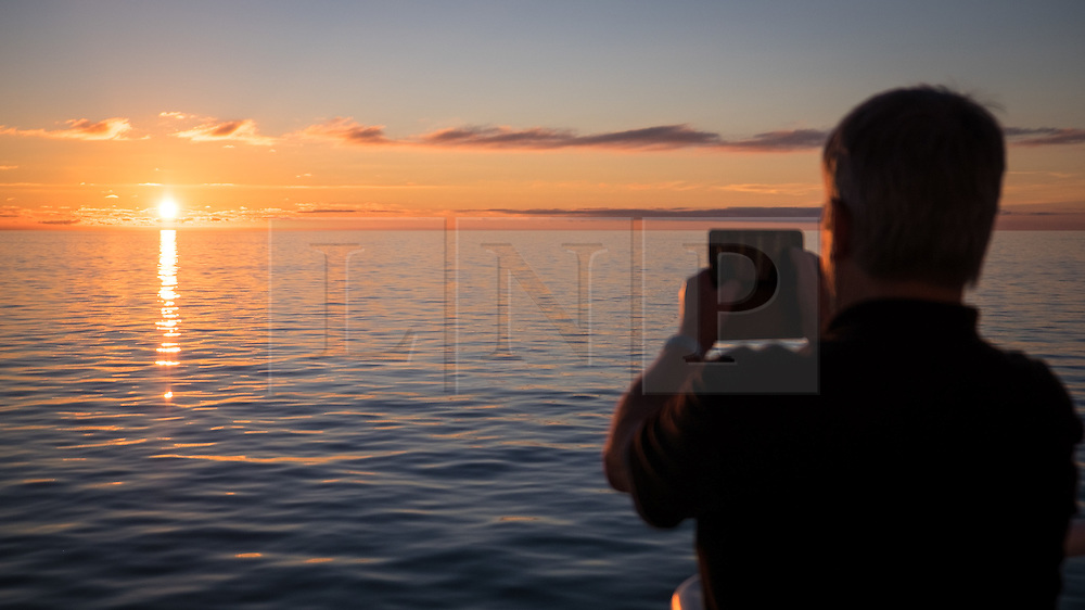 © Licensed to London News Pictures. 05/12/2016. Wick, UK.  A man takes a photo of the sunrise over the calm and glassy sea in the Moray Firth in Scotland this morning, 5th December 2016. The weather is set to be bright but cold in northern parts of the UK today, with milder weather forecast later in the week. Photo credit: Rob Arnold/LNP