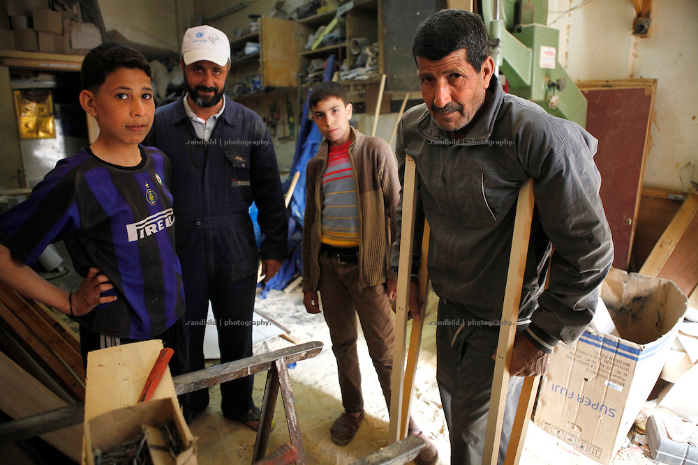 A neighbourhood initiative works in a little carpentry workshop and recycles former wooden sticks from pro-Assad banners to stretchers and brackets in order to give it for free to those who need it in Deir az-Zor. Residents of eastern syrian town Deir az-Zor joined arab spring protests against the regime of Bashar al-Assad from its early beginning in March 2011. Since summer 2012 the town with few hundred thousand inhabitants is embattled between the Syrian Army and different opposing rebel groups like Free Syrian Army and Jabhat al-Nusra. Deir az-Zor is target to constant shelling by artillery, war planes and short range missiles. Almost 70 percent of the town is rebel held while government forces remain in control over some residental areas and a strategic important airport. Deir az-Zor is widely damaged and some areas almost totally destroyed by fierce and long lasting battles. All direct road connections to Deir az-Zor are cut and fighters and returning residents as well depend on one provisional supply line across the Euphrates river which is regularly targeted by government snipers.