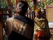 Laos - A Woman is listening to the advise of a monk