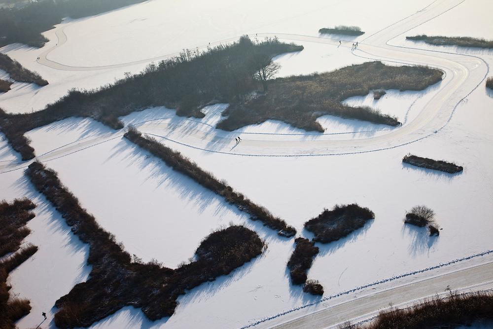 Nederland, Noord-Holland, Kortenhoefsche Plassen, 07-01-2010; schaatsers op de Kortenhoefse Plassen. Omdat de plassen relatief ondiep zijn zijn, zijn deze ondanks de sneeuw dichtgevroren en kan er geschaatst. De leden van de plaatselijk ijsclub Onderling Genoegen hebben met sneeuwschuivers sneeuw geruimd en er is een tocht uitgezet..Skaters on frozen lake near Amsterdam. Because the lake is relatively shallow it is frozen and, despite the snow, skating is possible. Members of the local skating club have cleared the snow with snowplows.luchtfoto (toeslag), aerial photo (additional fee required).foto/photo Siebe Swart