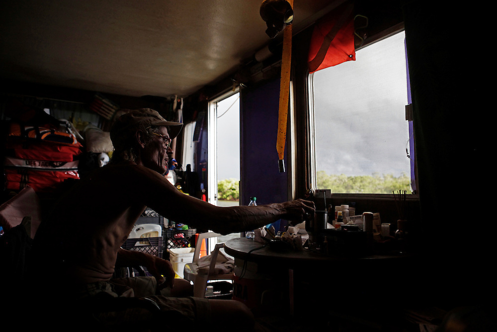 Scot Janikula, 50, who lives on his boat in Estero Bay, waits out a summer storm with his dog Renegade. Most who live on their boats have a plan for where to go during a tropical storm or hurricane, and many of the boats will withstand up to a category four storm.