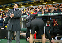 Fulham manager Chris Coleman rubs his hands before the start of the match as his assistant Steve Keen organises the seating arrangements.