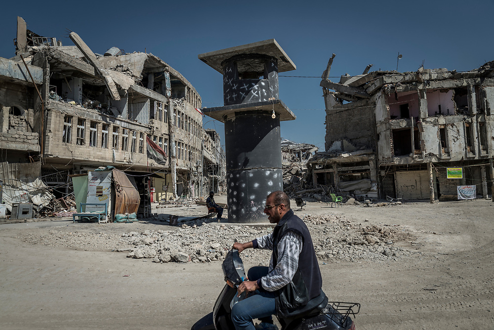 A man rides a scooter past a military checkpoint in the old city of Mosul. Residents claim that the bodies of 28 civilians are buried near the checkpoint, civilians who were executed by ISIS militants for attempting to flee.