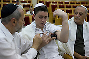 Israel, Tel Aviv, Beit Daniel, Tel Aviv's first Reform Synagogue Bar Mitzvah ceremony. Bar Mitzvah boy laying tefillin (phylacteries) during ceremony
