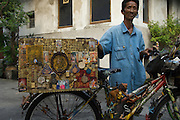 A trader of buddhist amulets plies his trade around the lanes of monks' quarters at Wat Mahathat.