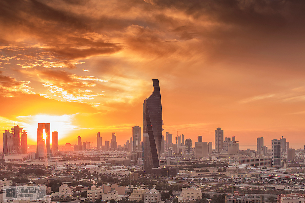 """Kuwait, officially the State of Kuwait i/kuːˈweɪt/ (Arabic: دولة الكويت Dawlat al-Kuwayt ), is a sovereign Arab state situated in the north-east of the Arabian Peninsula in Western Asia. It lies on the north-western shore of the Persian Gulf and is bordered by Saudi Arabia to the south (at Khafji) and Iraq to the north (at Basra). The name Kuwait is derived from the Arabic أكوات ākwāt, the plural of كوت kūt, meaning """"fortress built near water"""".[6] The country covers an area of 17,820 square kilometers (6,880 square miles) and has a population of about 3.5 million.[3]"""