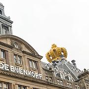 Amsterdam, 25-04-2013. Ter voorbereiding op de abdicatie/inhuldiging op 30 april zijn verschillende gebouwen, ondernemingen versiert. Op het dak van het magazijn De Bijenkorf op de Dam te Amsterdam, zijn twee grote opblaasbare kronen geplaatst,