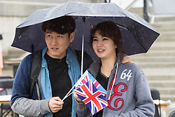 Trafalgar Square, London, June 12th 2016. Rain greets Londoners and visitors to the capital's Trafalgar Square as the Mayor hosts a Patron's Lunch in celebration of The Queen's 90th birthday. PICTURED: A couple watch the on-stage performances as the rain continues to fall.
