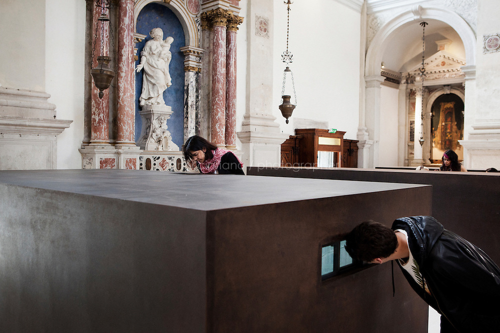 VENICE, ITALY - 29 MAY 2013: Visitors peer through a small aperture inside one of the six large iron boxes to see the diaroma contained within, part of &quot;S.A.C.R.E.D.&quot;, Ai Weiwei's new work shown at the Sant'Antonin's church in Venice, Italy, on May 29th 20113. <br /> <br /> &quot;S.A.C.R.E.D.&quot; (2013) is Ai Weiwei's new work addressing his 2011 arrest by the Chinese Government and the 81-day period subsequently spent in captivity. This is the first time the artist has directly responded to his incarceration through a work in a public exhibition. S.A.C.R.E.D. is composed of six parts: (i) S upper, (ii) A ccusers, (iii) C leansing, (iv) R itual, (v) E ntropy, and (vi) D oubt. This landmark work coprises six large iron boxes with small apertures - such as those found in the door of a cell - though which the viewer must peer to see the dioramas contained within. Each diorama includes large hyper-realist models of the artist and his captors, and documents the different stages of Ai Weiwei's time in incarceration.<br /> <br /> The 55th International Art Exhibition of the Venice Biennale takes place in Venice from June 1st to November 24th, 2013 at the Giardini and at the Arsenale as well as in various venues the city. <br /> <br /> Gianni Cipriano for The New York TImes