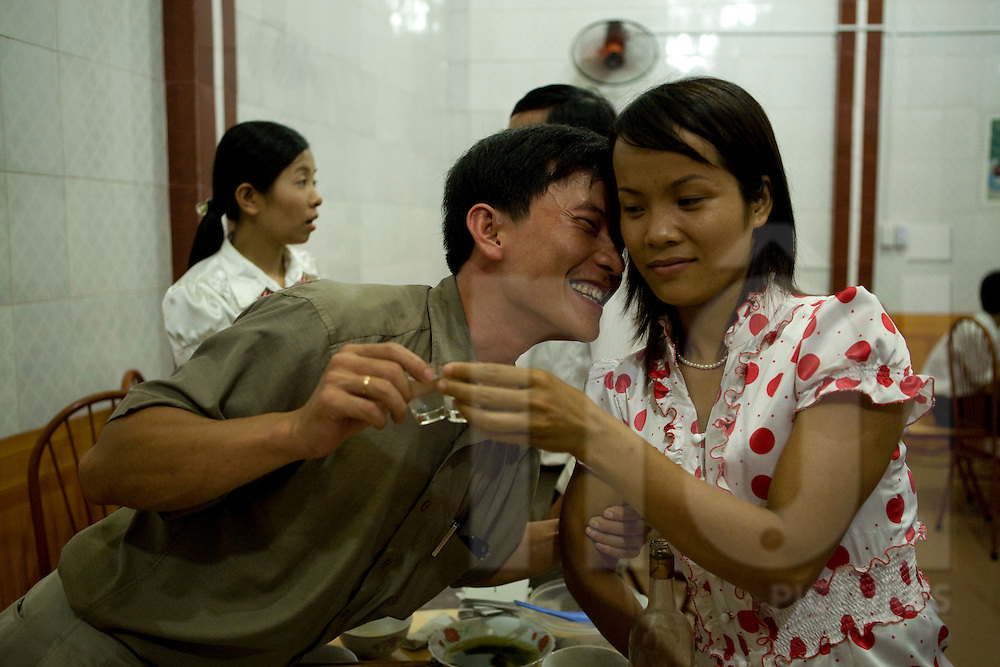 A drunk man is flirting with a vietnamese woman during a party. They cheers with some rice wine. Yen Bai province, Vietnam, Asia.
