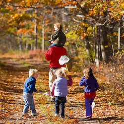 A man carries his son(age 4) on his shoulders on a woodland trail in Biddeford, Maine. Three children follow.