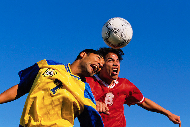 Soccer Players Heading Ball --- Image by © Jim Cummins/CORBIS