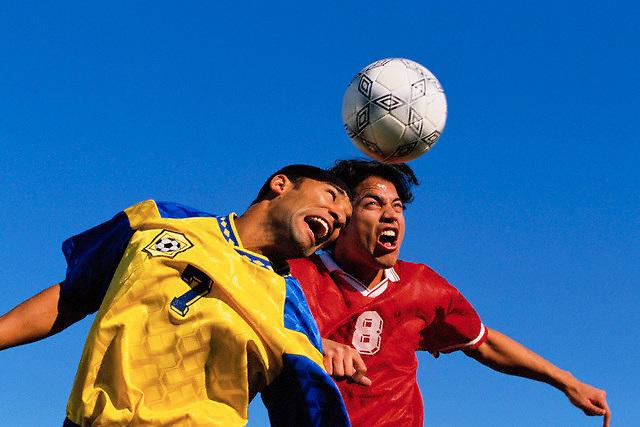 Soccer Players Heading Ball --- Image by © Jim Cummins/CORBIS