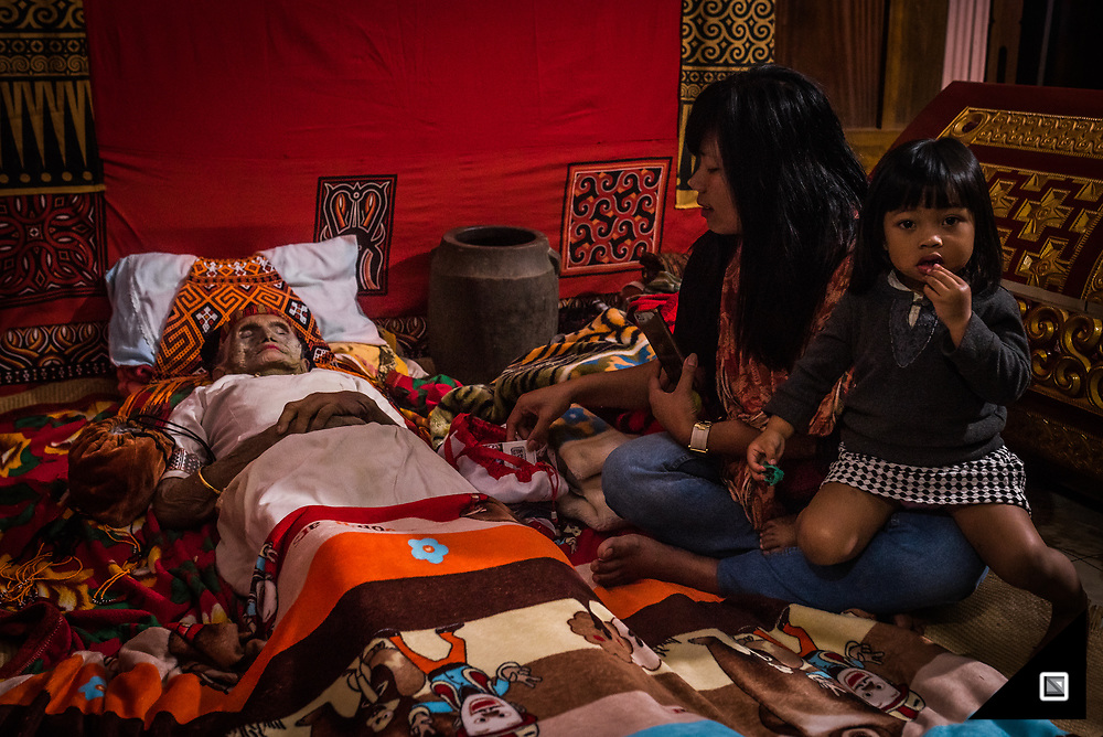 Relatives visit Nene' Tiku who passed away 3 days ago in the age of 106. Her relatives believe, Nene' Tiku is only sick - not dead (Toma Kula'). Torajans learn from a very young age to deal with death and to accept it as part of the journey. In Toraja, it' is customary to feed the deceased every day and to keep the corpses cozily bedded in a separate room of the family house until the family can afford a proper funeral which easily costs 50'000 to 500'000 USD depending on the caste of the family and how may buffalos they have to sacrifice.