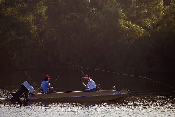 Stock photo of two men fishing from their boat in a lake