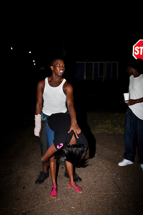 """Demetrius """"Butta"""" Anderson, 18, jokingly bends a girl over while horsing around on the corner of Young and Pelican in the Baptist Town neighborhood of Greenwood, Mississippi on Sept. 24, 2010. Butta's arm is in a cast from a recent fight. About one month later Butta is murdered by a man he has been beefing with across the tracks."""
