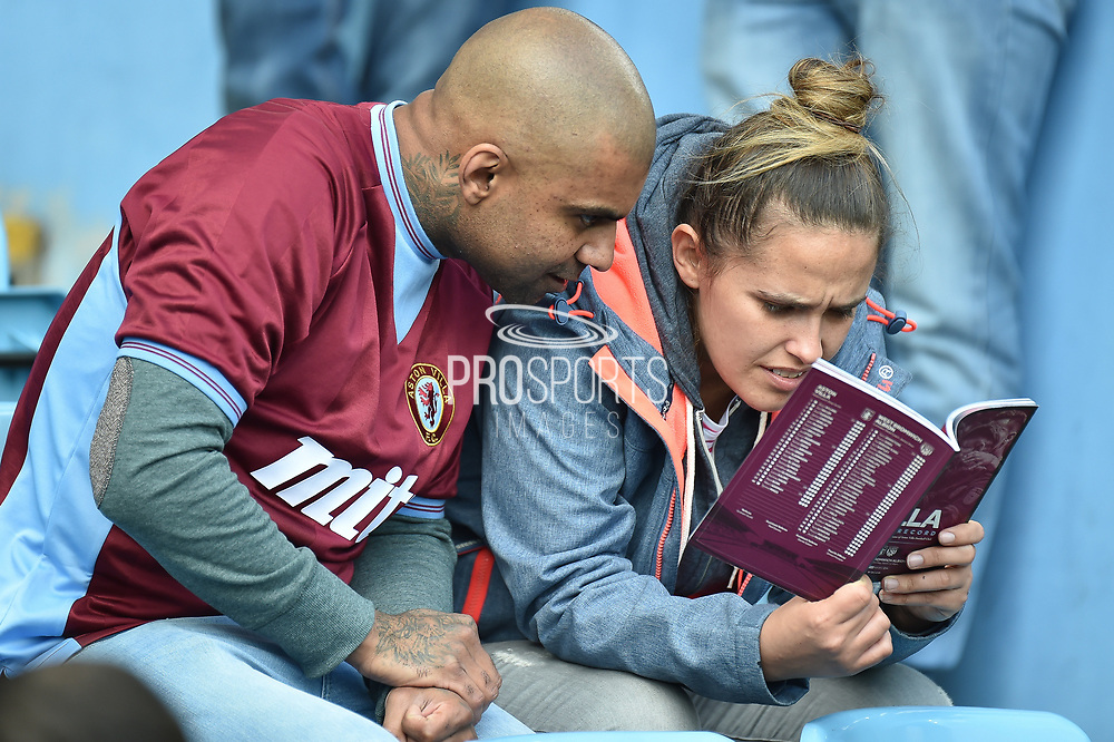 A young couple in the crowd read the match programme together during the EFL Sky Bet Championship first leg Play Off match between Aston Villa and West Bromwich Albion at Villa Park, Birmingham, England on 11 May 2019.