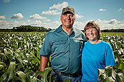 Rural lifestyle farm couple portrait, standing in Midwestern corn field, early summer.