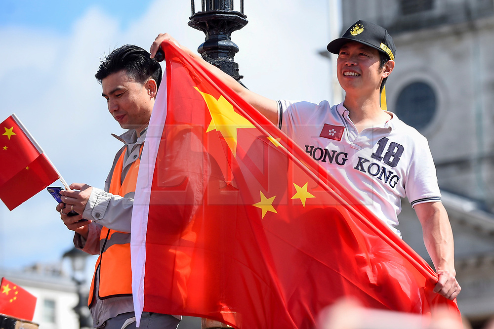 © Licensed to London News Pictures. 18/08/2019. LONDON, UK.  A member of the capital's Chinese community wearing a Hong Kong T-shirt waves a Chinese flag during a rally in Trafalgar Square to support the people of Hong Kong and China.  They are calling for an end to police violence and a respect for law as protests in the former British colony enter their eleventh week.  Photo credit: Stephen Chung/LNP