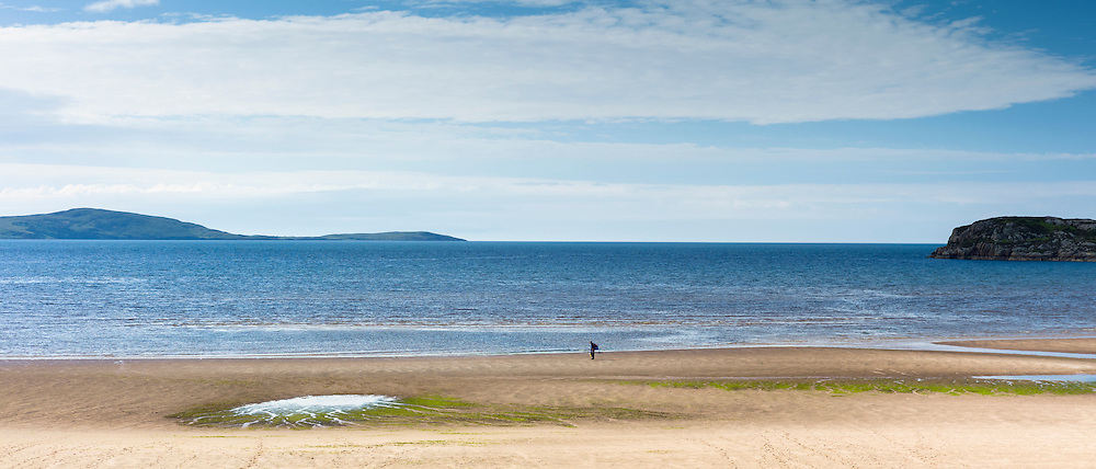 Lone figure, a fisherman, strolls along Little Gruinard remote sandy beach in the West Coast of Scotland