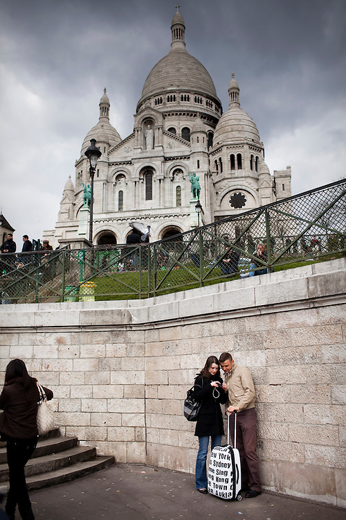 A vacationing couple look through photos on their camera near Sacre Coeur in Montmartre in Paris.