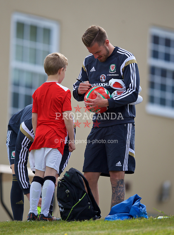 CARDIFF, WALES - Monday, June 8, 2015: Wales' Aaron Ramsey signs an autograph for a supporter before a training session at the Vale of Glamorgan ahead of the UEFA Euro 2016 Qualifying Round Group B match against Belgium. (Pic by David Rawcliffe/Propaganda)