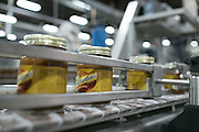 Newly labeled jars of Mrs. Richardson's Butterscotch Caramel topping move down the conveyer at Baldwin Richardson Foods in Macedon on Friday, August 21, 2015.