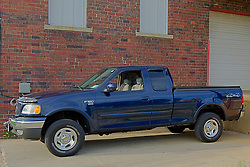 30 May 2014:   2003 Ford F 150 XLT 4x4 (four wheel drive) extended cab pick up truck in blue with high polish chrome wheels and Michelin raised white letter all whether tires.  Truck sports seat covers and a folding soft bed cover.<br /> <br /> This image was produced in part utilizing High Dynamic Range (HDR) processes.  It should not be used editorially without being listed as an illustration or with a disclaimer.  It may or may not be an accurate representation of the scene as originally photographed and the finished image is the creation of the photographer.