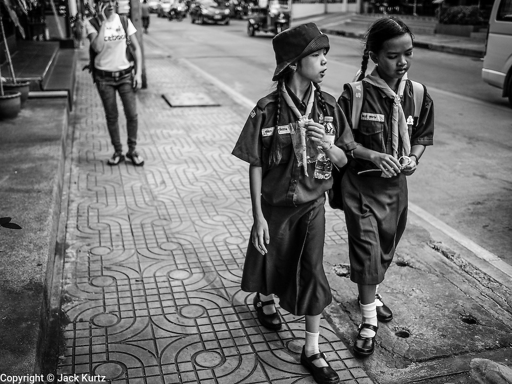 18 JULY 2013 - BANGKOK, THAILAND:   Girl Scouts who are students at Sai Nam Peung School walk home after school. Sai Nam Peung School is one of the elite schools in Bangkok. It was established in 1961 and has more than 3500 students. Although it's a public school, only students from elite families go to the school.     PHOTO BY JACK KURTZ