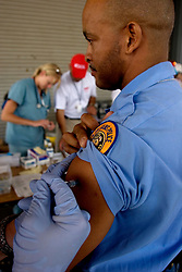 10 Sept 2005. New Orleans, Louisiana.  Hurricane Katrina aftermath.<br /> NOPD officer Matt Robinson is injected with a tetanus shot by the Mobile Medical Response team at the bottom of Canal Street.<br /> Photo; ©Charlie Varley/varleypix.com