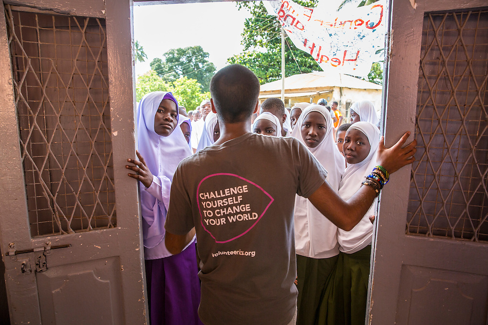 VSO ICS volunteer Bharat Thakrar welcomes the children of the community for the first part of the VSO ICS Community Action Day CAD in Y2K Hall Lindi, Lindi region. Tanzania.