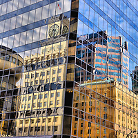 Reflection of Vancouver Clock Tower at Granville and Broadway in Vancouver, Canada <br /> Downtown Vancouver, Canada is a sea of beautiful, modern and glass skyscrapers.  In the Vancouver Block neighborhood is a 15 story building with white, terra cotta cladding.  Atop this 1912 Edwardian landmark sits the Vancouver Clock Tower.  This photo reflects the multi-generational architectural styles that grace the City of Vancouver in British Columbia.