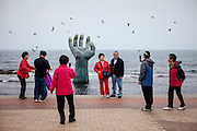"""People are photographing each other in front of the so called """"Hand of Harmony"""" at Homigot beach close to Pohang at the South Korean East coast."""