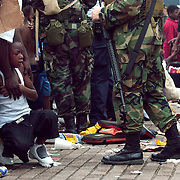 CAPTION: (9/01/2005)<br /> A young boys stricken by fear and the effects of heat and humidity is helped by other evacuees while Nations Guard troops watch during the evacuation of Superdome after on Thursday morning.  The destruction caused by Hurricane Katrina has left New Orleans and it's inhabitants in primitive conditions.<br /> (Times photo by Willie J. Allen Jr.)