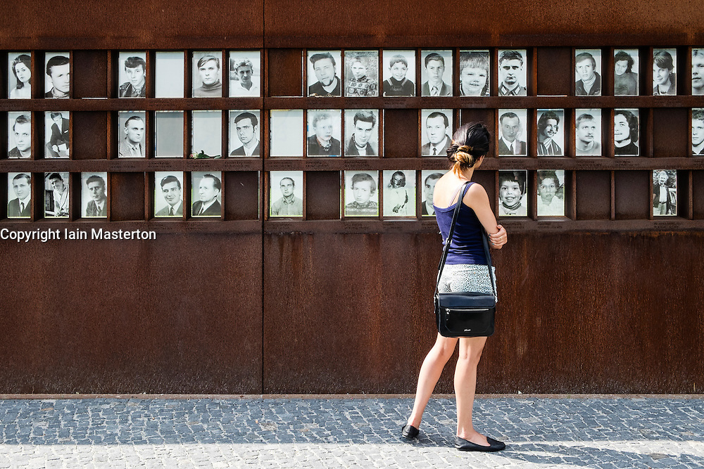 Woman looking at photographs of victims of escape attempts across Berlin Wall at Bernauer Strassse Memorial Park in Berlin Germany