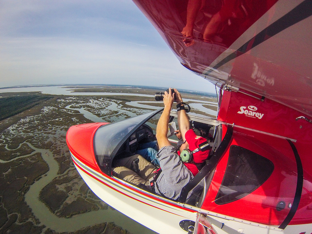 Photographer holding camera out of seaplane window while flying in Southeastern USA