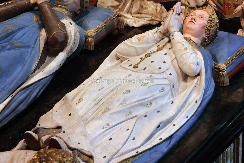 Effigy of Margaret of Bavaria, from the tomb of Jean sans Peur, or John the Fearless, 1371-1419, (Jean de Valois or John of Valois, Jean I, duc de Bourgogne, or John I, Duke of Burgundy) and his wife Marguerite de Baviere, or Margaret of Bavaria, 1363- 1423, 1443-70, by Jean de la Huerta, 1413-62, and Antoine le Moiturier, 1425-97, in the Grande Salle du Palais des ducs de Bourgogne, or Salle des Gardes, a 15th century Flamboyant Gothic hall, in the Musee des Beaux-Arts de Dijon, opened 1787 in the Palace of the Dukes of Burgundy in Dijon, Burgundy, France. The tomb consists of painted alabaster effigies with lions and angels, and below, figures of pleurants or weepers among Gothic tracery. The tomb was begun in 1443 (24 years after his death), by Jean de La Huerta, and Antoine le Moiturier after 1456, and finally installed in 1470. The tombs were originally from the Chartreuse de Champmol, or Chartreuse de la Sainte-Trinite de Champmol, a Carthusian monastery which was sacked in the French Revolution and the tombs moved to Dijon cathedral then here in 1827. The effigies are 19th century reconstructions, the originals being destroyed in the French Revolution. Picture by Manuel Cohen