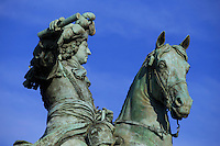 A bronze statue of Louis XIV astride a horse in front of the Chateau Versaille on the outskirts of Paris, France.