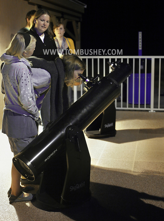 New Paltz, New York - Observatory director Amy Forestell watches as a woman looks a the moon through a Dobsonian telescope during International Observe the Moon Night at Smolen Observatory at SUNY New Paltz  on Sept. 18, 2010.