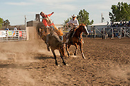 Sawyer Stotts; bareback rider after successful ride; Jay Shaw, pickup man, Miles City Bucking Horse Sale; Montana; MODEL RELEASED on two riders only.