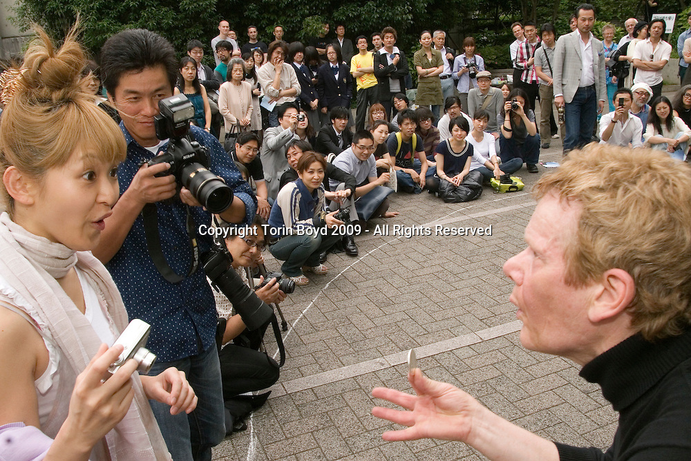 This is world famous French high wire artist Philippe Petit in Japan during a promotional tour for the documentary film about about him called Man on Wire. This film by UK director James Marsh will premier in Japan on July 4, 2009 and has garnered several prestigious awards including: the World Cinema Jury and Audience award at the Sundance Film Festival in 2008; the 2008 Full Frame Documentary Film Festival in Durham, N.C.; and the 2009 Academy Award for Best Documentary. Petit is also an Artists-in-Residence at the Cathedral of St. John the Divine in New York City and currently lives in Woodstock, New York. He is seen here giving an impromptu street performance in a small Tokyo park located in the Shibuya neighborhood on May 19, 2009.