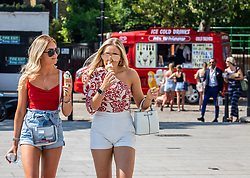 © Licensed to London News Pictures. 23/06/2020. London, UK. Sophie Taylor and Neve Foster both 18 enjoy an ice cream in the sunshine along the Richmond Riverside in South West London as forecasters predict a hot week ahead with temperatures expected to reach over 30c. Prime Minister, Boris Johnson announces that tourism and hospitality including pubs, restaurants and campsites can now reopen from the 4th of July as well as reducing the 2 metre rule to 1 metre.  Photo credit: Alex Lentati/LNP <br /> <br /> *Permission Given*