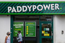 © Licensed to London News Pictures. 14/06/2020. London, UK. Members of the public wearing face coverings walk past a branch of PaddyPower in north London which will reopen on 15 June as coronavirus lockdown restrictions are eased. The government has announced that all betting shops can re-open on Monday 15 June. Betting shops were closed late March following outbreak of COVID-19. Photo credit: Dinendra Haria/LNP