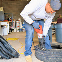 Cornfields Chapter maintenance worker Vernell Joe cuts out the side of a truck tire. Both sides will be cut out. To Joe's left is a pile of tire sides that have been cut and are ready for washing.