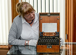 Pictured: Susan Bouwens from Bonham's in Glasgow with a very rare German Enigma code machine from 1941, expected to fetch up to £150000 GBP at auction in October.<br /> <br /> © Dave Johnston / EEm