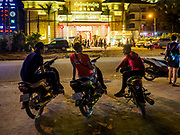 "13 FEBRUARY 2019 - SIHANOUKVILLE, CAMBODIA:  Cambodian motorcycle taxi drivers wait for fares across the street from the New MGM Casino, a Chinese owned casino in Sihanoukville. There are about 80 Chinese casinos and resort hotels open in Sihanoukville and dozens more under construction. The casinos are changing the city, once a sleepy port on Southeast Asia's ""backpacker trail"" into a booming city. The change is coming with a cost though. Many Cambodian residents of Sihanoukville  have lost their homes to make way for the casinos and the jobs are going to Chinese workers, brought in to build casinos and work in the casinos.      PHOTO BY JACK KURTZ"