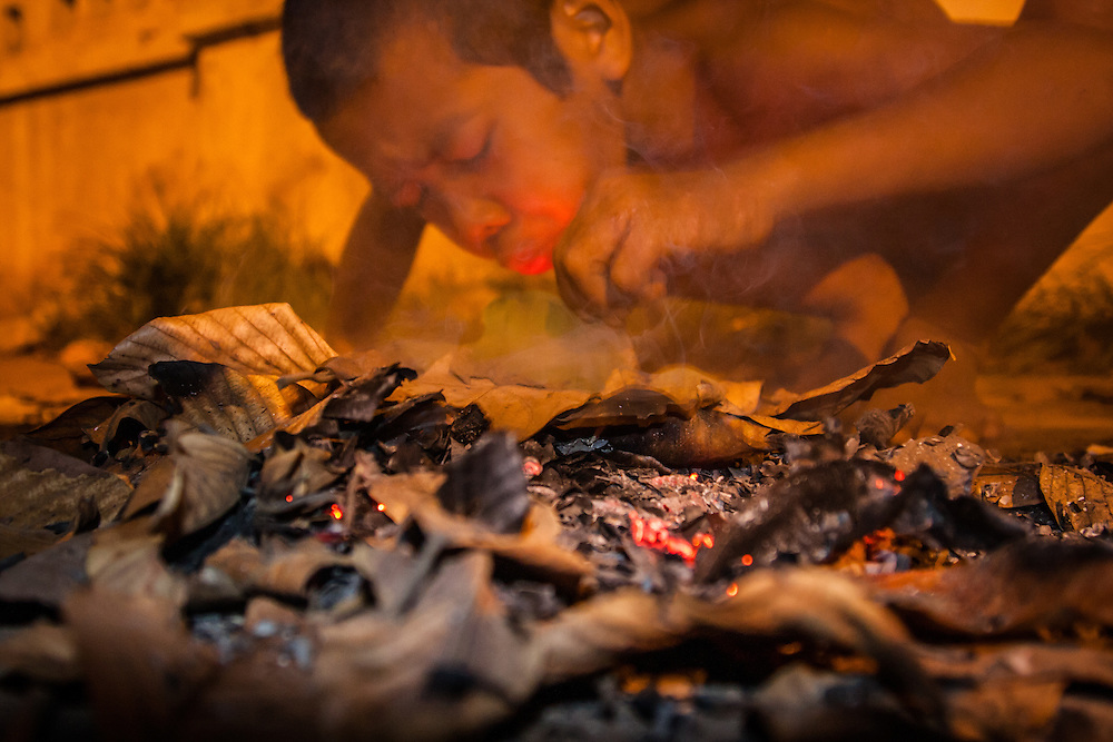 A homeless boy makes a fragile fire from leaves on a streetside in Siem Reap, Cambodia.