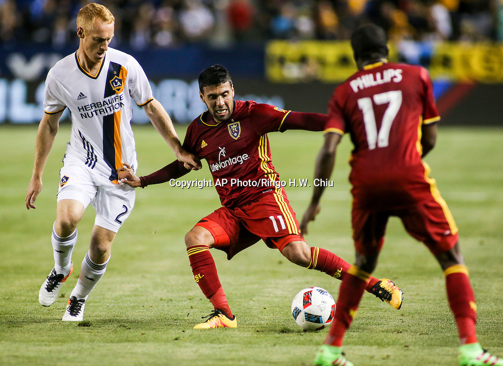 Real Salt Lake midfielder Javier Morales, center, controls the ball against Los Angeles Galaxy midfielder Jeff Larentowicz, left, in the second half of an MLS soccer game in Carson, Calif., Saturday, April 23, 2016. The Galaxy won 5-2. (AP Photo/Ringo H.W. Chiu)