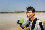 "28 MARCH 2014 - NA KHOK, SAMUT SAKHON, THAILAND: A Burmese migrant laborer drinks a glass of water during a break on a Thai salt farm in Samut Sakhon province. Thai salt farmers south of Bangkok are experiencing a better than usual year this year because of the drought gripping Thailand. Some salt farmers say they could get an extra month of salt collection out of their fields because it has rained so little through the current dry season. Salt is normally collected from late February through May. Fields are flooded with sea water and salt is collected as the water evaporates. Last year, the salt season was shortened by more than a month because of unseasonable rains. The Thai government has warned farmers and consumers that 2014 may be a record dry year because an expected ""El Nino"" weather pattern will block rain in mainland Southeast Asia. Salt has traditionally been harvested in tidal basins along the coast southwest of Bangkok but industrial development in the area has reduced the amount of land available for commercial salt production and now salt is mainly harvested in a small parts of Samut Songkhram and Samut Sakhon provinces.    PHOTO BY JACK KURTZ"