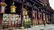 """Kitano Tenmangu Shrine is dedicated to Sugawara Michizane, a scholar and politician who was unfairly exiled by his political rivals. A number of disasters were attributed to Michizane's vengeful spirit after his death in exile, and these shrines were built to appease him. Kyoto, Japan. The decorative white round empty liquor barrels at Japanese shrines are kazaridaru, shrine offerings from Japan's nihonshu makers. In Japanese, the word sake (""""liquor"""", also pronounced shu) can refer to any alcoholic drink, while the beverage called """"sake"""" in English is usually termed nihonshu (""""Japanese liquor"""" or Japanese rice wine). In traditional Japanese culture, nihonshu is believed to connect people directly to the gods, as in Shinto ceremonies at weddings, during New Year celebrations and at many festivals. In modern times the kazaridaru are usually offered empty, with the nihonshu maker also providing one bottle of their best rice wine as part of the offering. The offering is a form of prayer for bountiful harvests of rice, and also honours the shrine's local deity. The kanji on the decorative barrels indicate the maker's name and location."""
